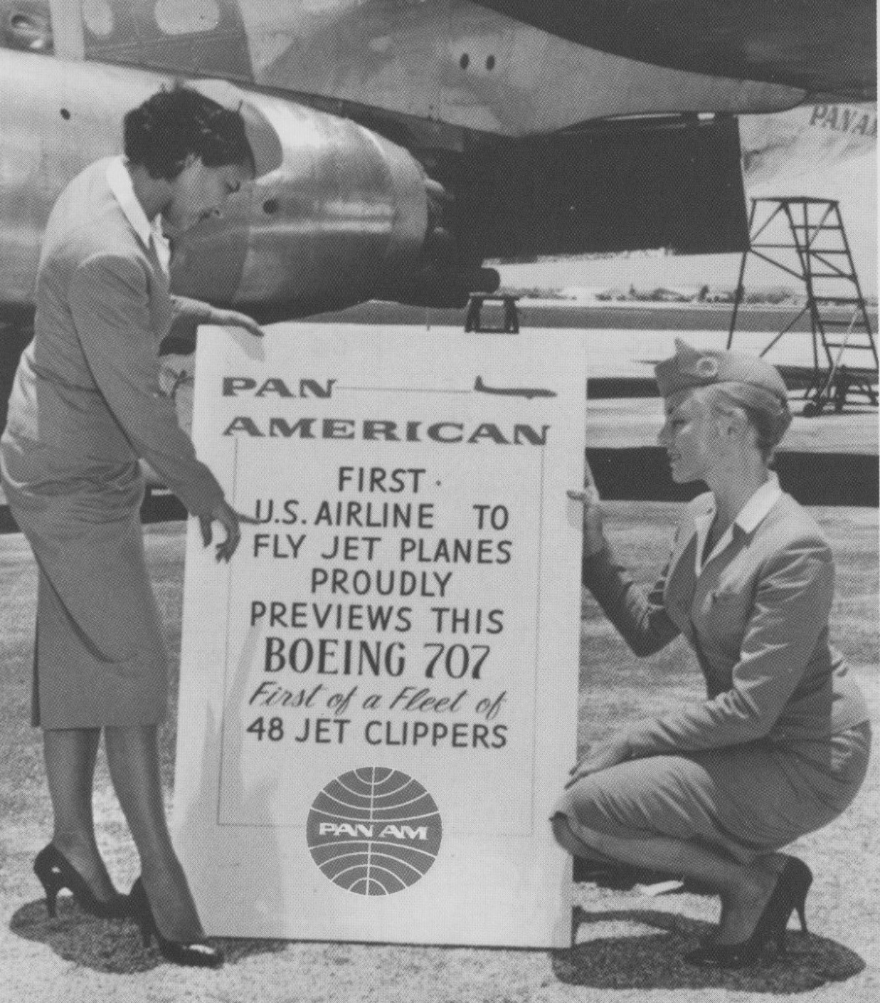 1950s Two stewardesses review a sign by an early Pan Am jet Clipper