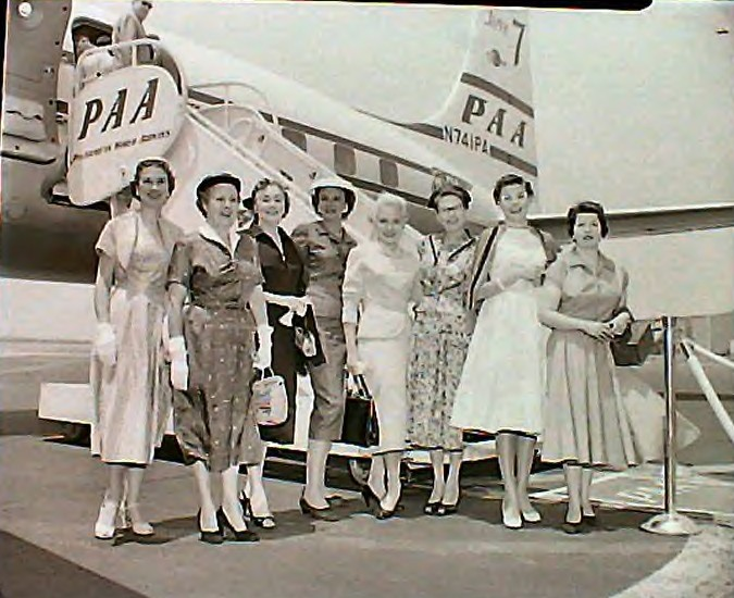 1950s Group of customers pose by the tail of a DC7 Clipper.