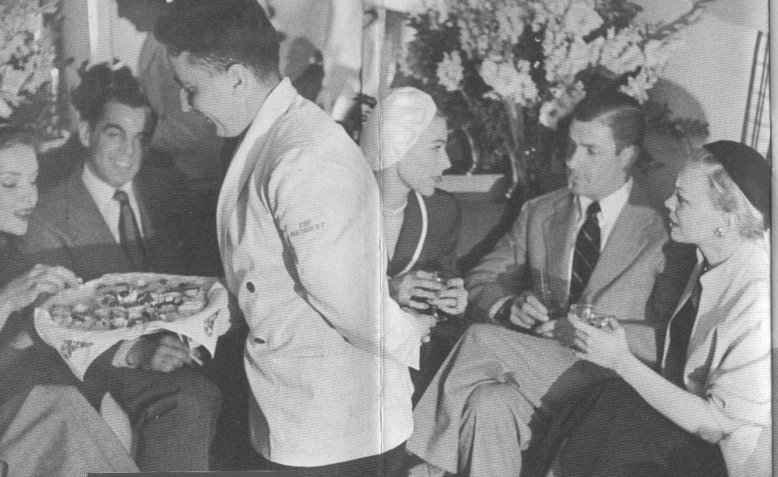 1950s A steward in white serving jacket offers snacks to customers in the lower deck lounge of a Pan Am Boeing 377 Stratocruiser.
