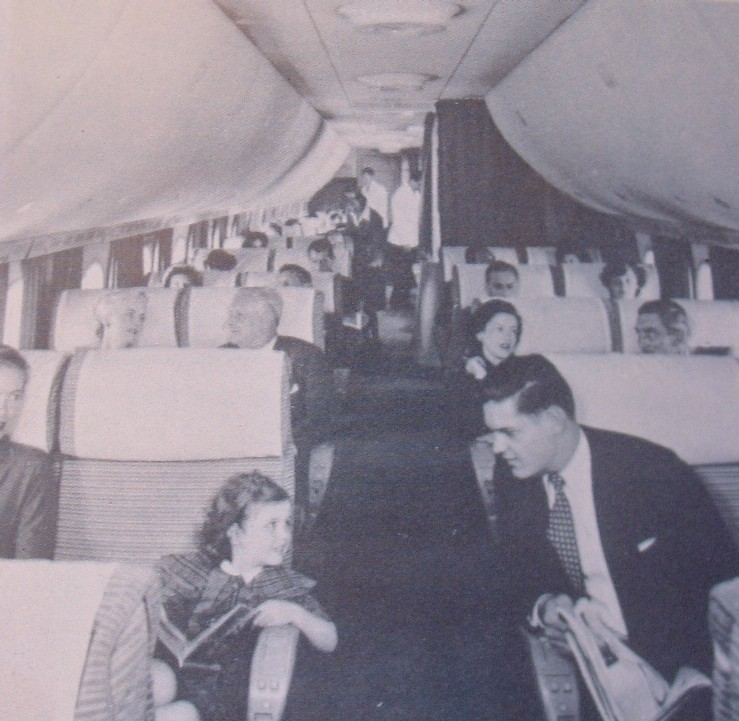 1950s Young lady & gentleman visit across the aisle of a Boeing 377 Stratocruiser