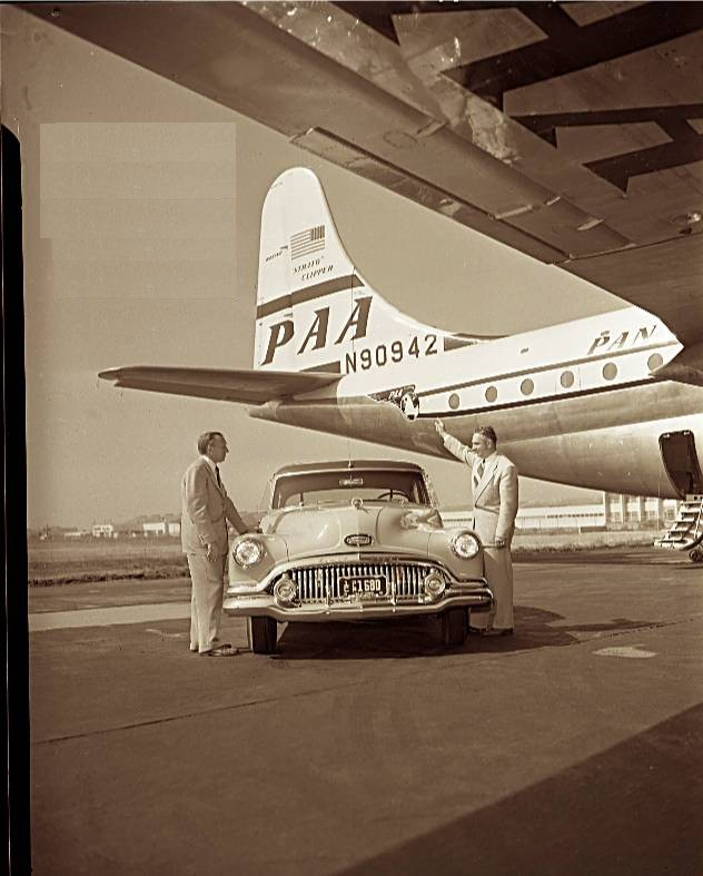 1950s A Pan Am Boeing 377 Stratocruiser serves as a back drop for a vehicle and passengers.