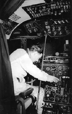 1950s A Pan Am mechanic working in the cockpit of a DC4 Clipper at Berlin Tempelhof airport.