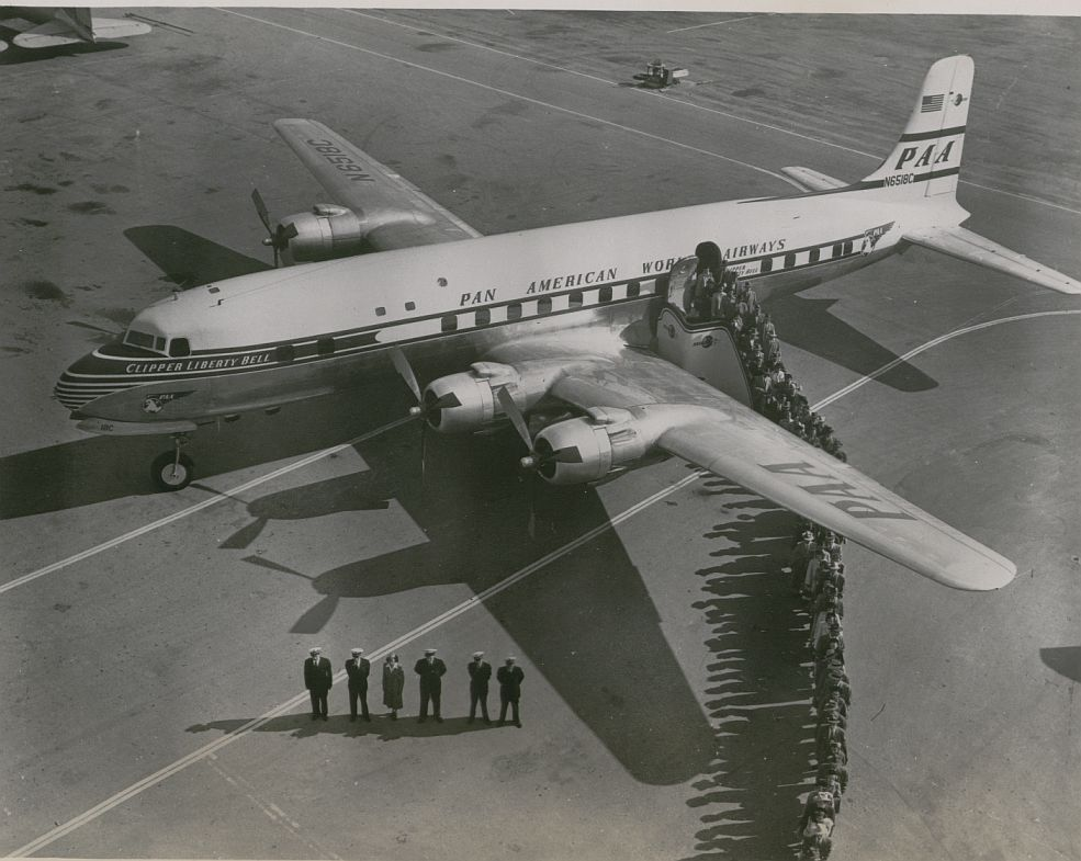 1950s Crew and customers line up on the ramp next to a Pan Am DC6 Clipper.