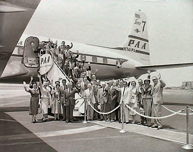 1950s Customers pose and wave on the ramp next to a Pan Am DC7  Clipper.