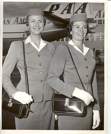 1950s Two Pan Am Stewardesses in full uniform of the era show their white smiles & gloves with a Boeing 377 Stratocruiser in the background.