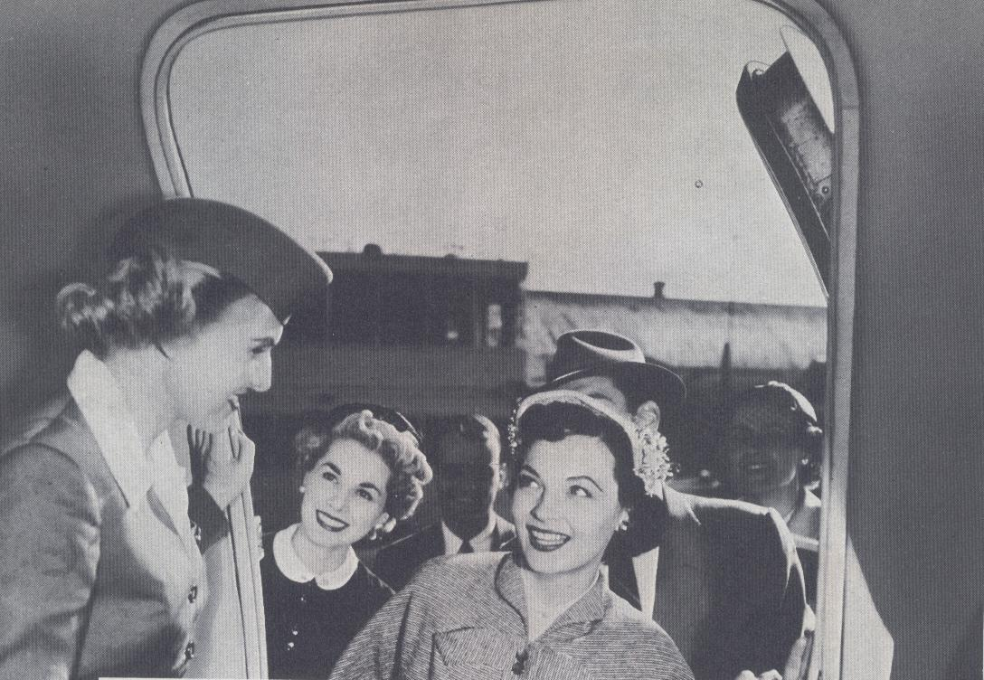 1950s A stewardess greets customers in the doorway of a Pan Am Clipper.