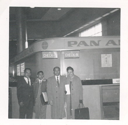1950s A family posing at a Pan Am ticket counter.