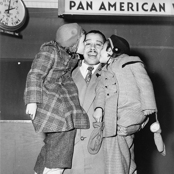 1951 Cab Caloway and children at at Pan Am ticket counter.