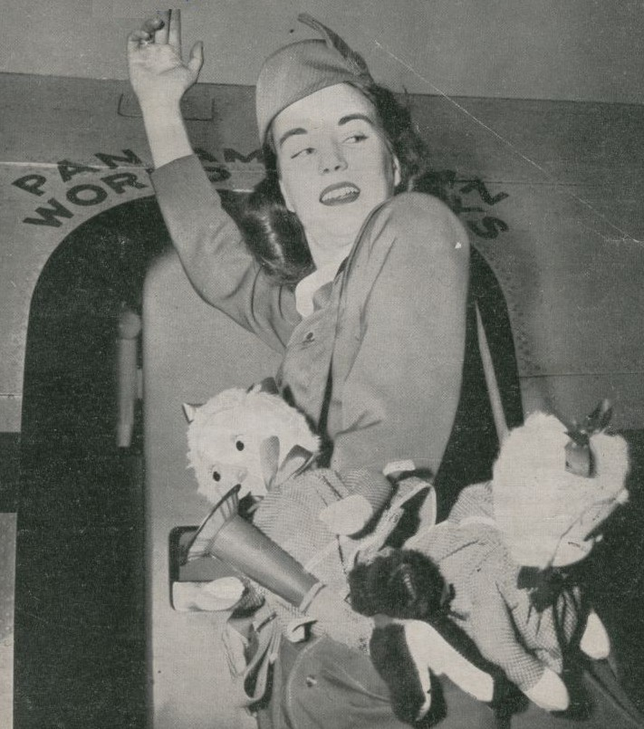 1952 Pan Am Stewardess boards an aircraft with charity toys for children at one of her ports of call.