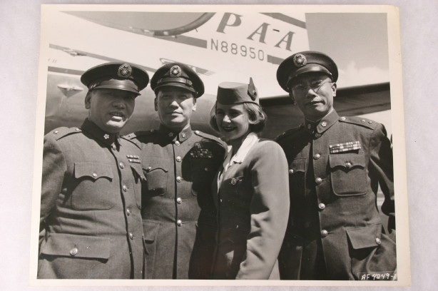1953 Pan Am stewardess  posing with 3 men in uniform with a Boeing 377 Stratocruiser in the background.