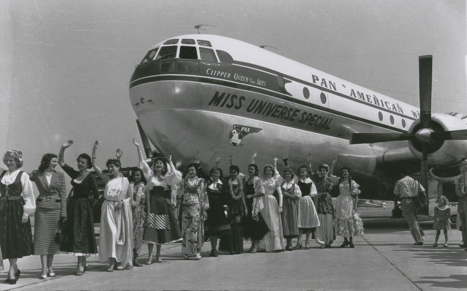 1953 Pan Am renames a Boeing 377 Stratocruiser for the Miss Universe competition while some of the contestants pose by the aircraft.