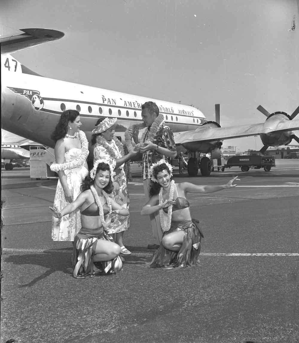 1954 Hula girls with a Pan Am Beoing 377 Stratocruiser in the background.