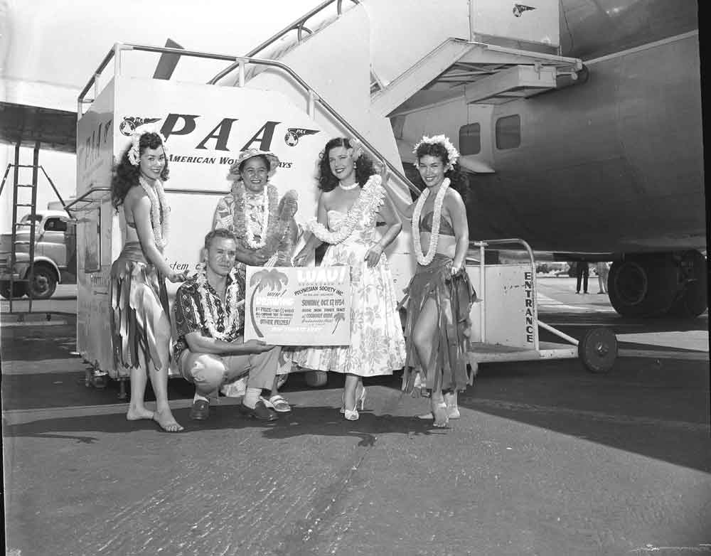 1954 Hula Girls pose by the stairway to a Pan Am Boeing 377 Stratocruiser.