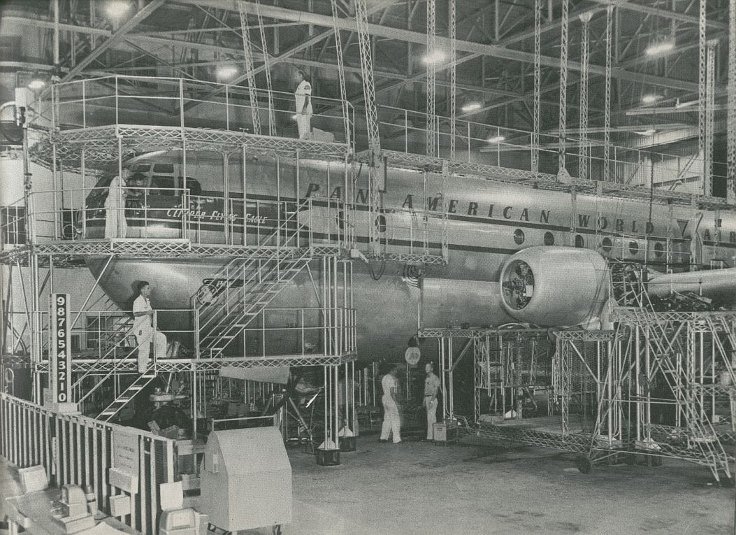 1956 A Pan Am Boeing 377 Stratocruiser in hanger maintenance scaffolding.