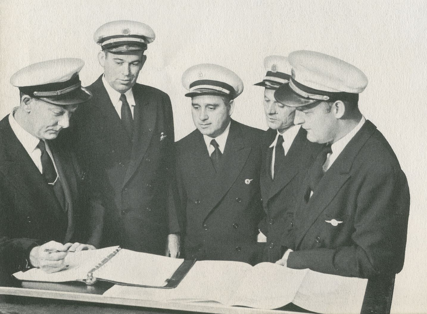 1956 Pan Am pilots gather before a flight to discuss weather and the route plan.  Pilot Victor Grubbs is second from left.