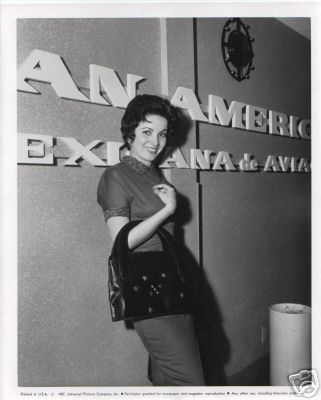 1957 A woman posing by the Los Angeles Airport Pan Am ticket counter.
