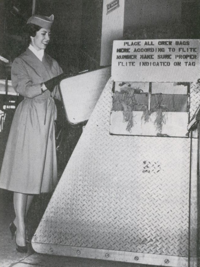 1959 A Pan Am stewardess tags her own suitcase on the ramp at New York JFK airport.