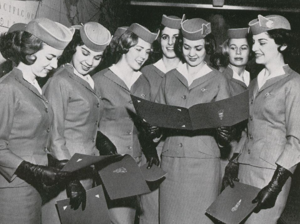1959 A group of newly hired stewardesses review their diplomas on graduation day.