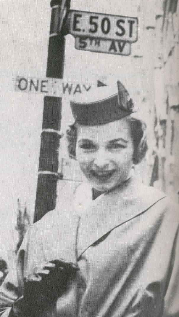 1959 A Pan Am stewardess at the corner of 5th Avenue & 50th Street in New York City.