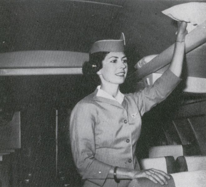 1959 A Pan Am stewardess reaches for a pillow in the cabin of a Boeing 707.