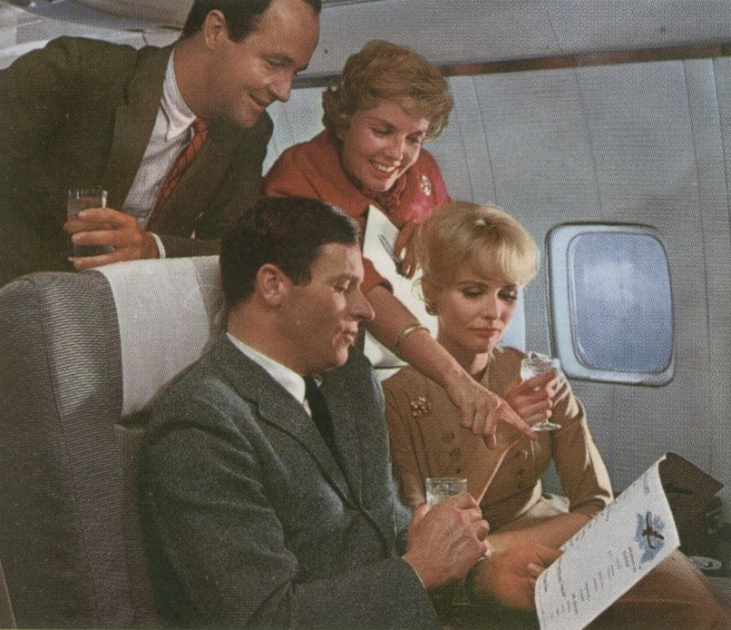 1959 First Class customers review the dinner menu on a Pan Am Boeing 707 jet.