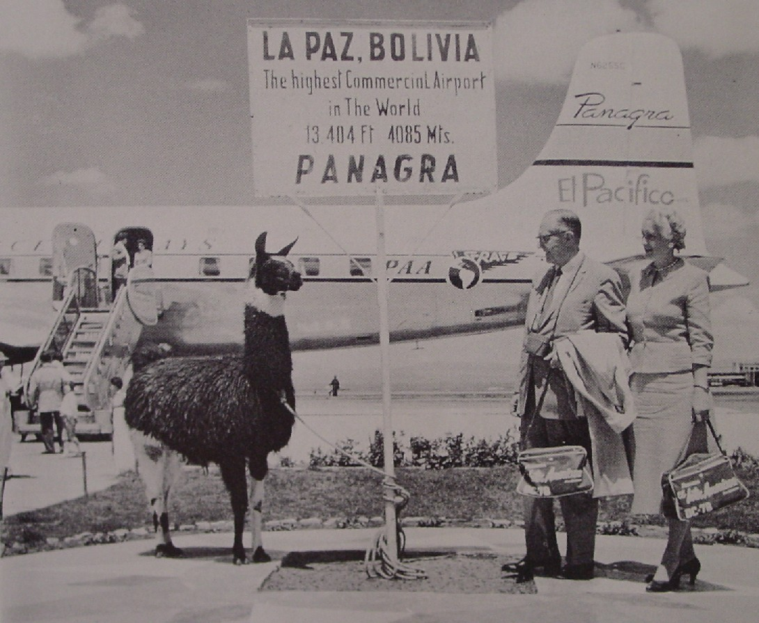 1959 Customers and a llama pose for a picture at the airport in LaPaz Bolivia with an aircraft of sister company Panagra in the background.