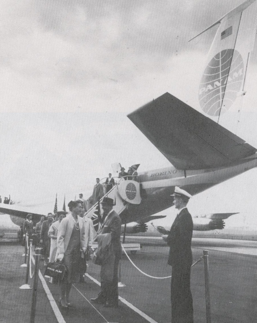 1959 Customers deplane the rear door of a Pan Am  707 onto a painted ramp walkway.